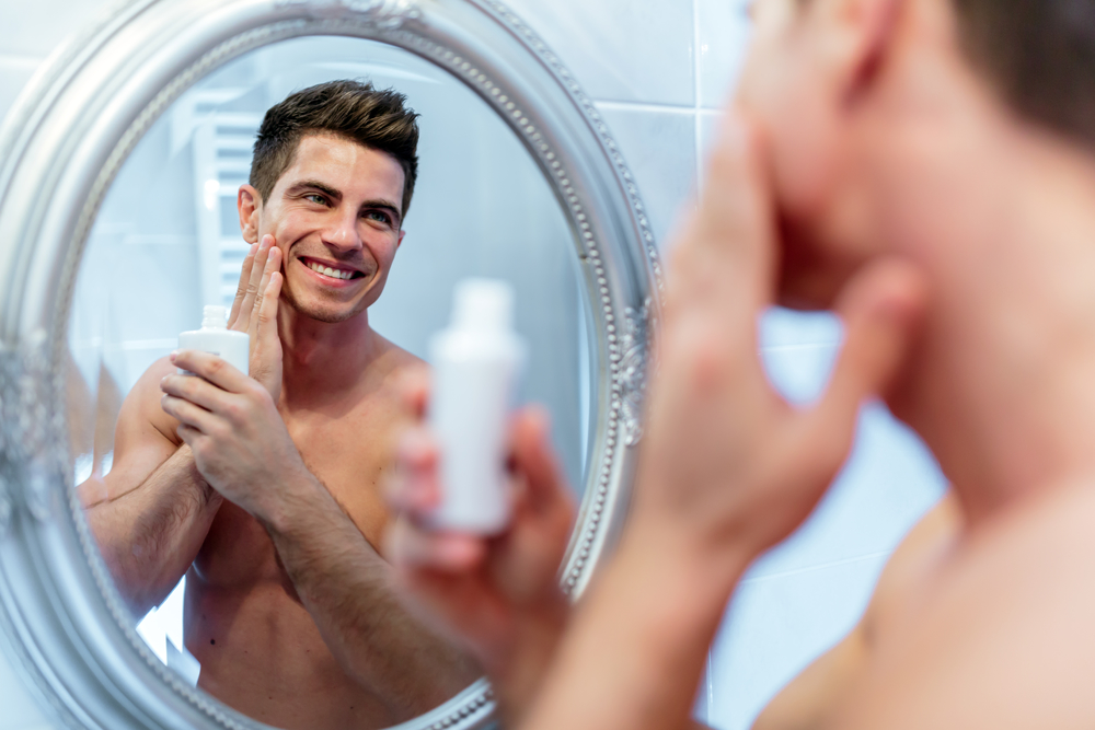man in the mirror applying lotion to his face