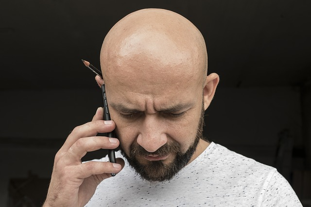 bald man talking on cell phone